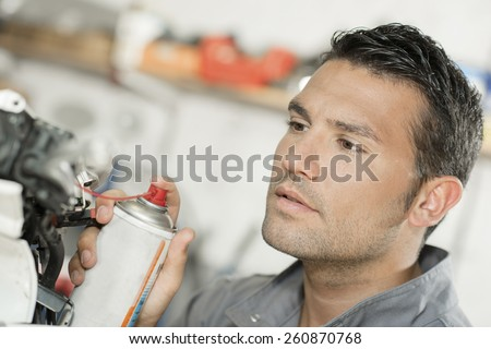 Mechanic working on a scooter - stock photo
