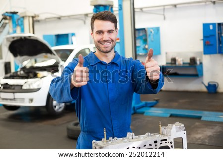 Mechanic working on an engine at the repair garage - stock photo