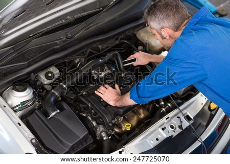 Mechanic working under the hood at the repair garage - stock photo
