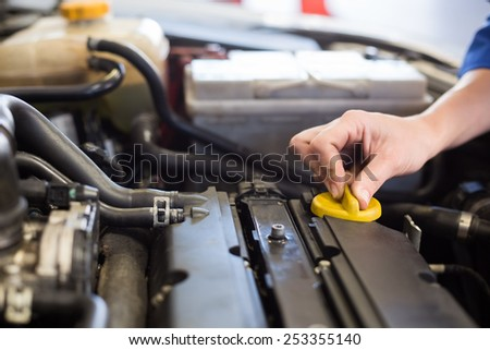 Mechanic working under the hood at the repair garage