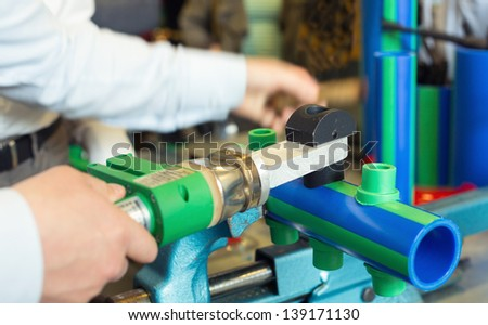 Mechanic working with pipes at workroom - stock photo