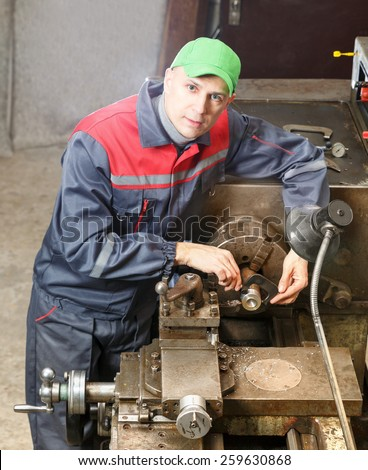 mechanic works at the lathe.metal processing - stock photo