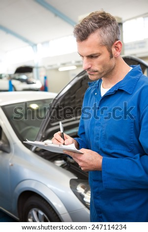 Mechanic writing on a clipboard at the repair garage