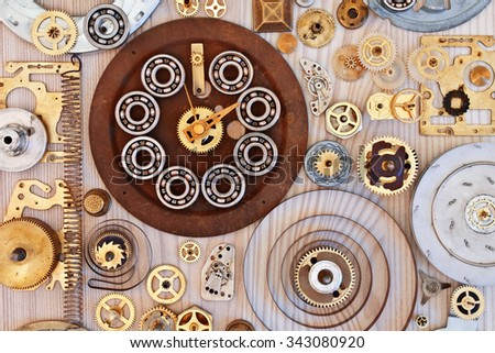 Mechanical collage with different items. Various metal parts on wooden background