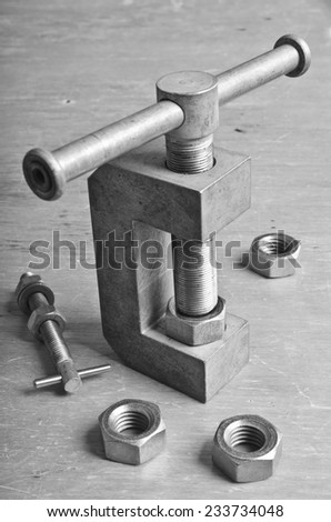 Mechanical device for threading in the nut is on the desktop environment tools - stock photo