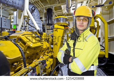 Mechanical engineer posing in the engine room of an offshore supply vessel - stock photo