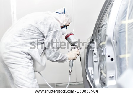 mechanical engineer working on painting a car in a painting booth