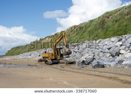 mechanical excavator working on coastal protection for the ballybunion golf course in ireland - stock photo