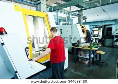 mechanical industrial worker at cnc milling machine center in tool manufacture workshop. Authentic shooting in challenging conditions. - stock photo