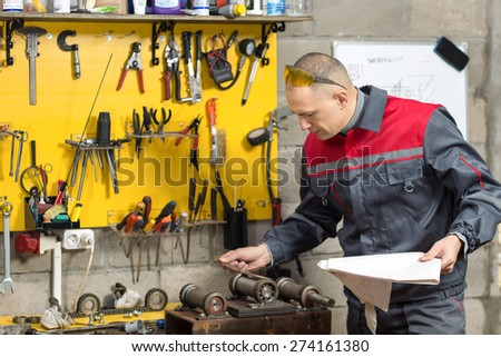 mechanical technician measuring cutting tool  at tool workshop