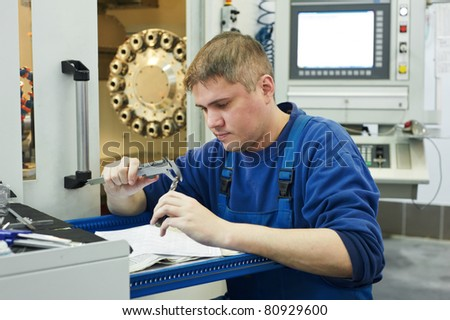 mechanical technician measuring detail after cnc milling cutting machine center at tool workshop - stock photo