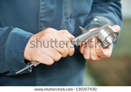 mechanical technician worker hands measuring detail tool after processing at workshop with sliding caliper at manufacturing - stock photo