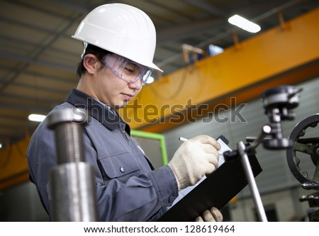 Mechanical technician writing on notepad in the factory