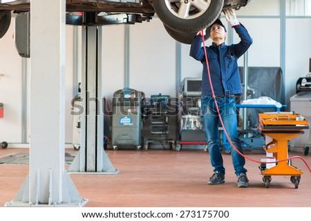 Mechanici changing car wheel in auto repair shop - stock photo