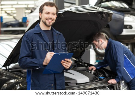 Mechanics at repair shop. Cheerful young mechanic writing something in his clipboard while another one fixing a car on the background - stock photo