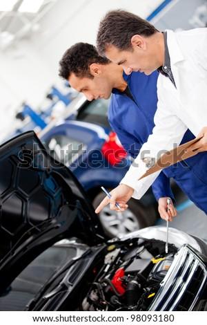 Mechanics fixing a at at the repair shop - stock photo