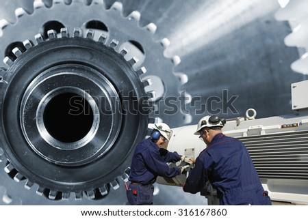 mechanics, workers with giant cogwheels axle machinery - stock photo