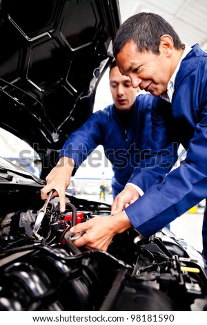 Mechanics working at the garage and fixing a car - stock photo