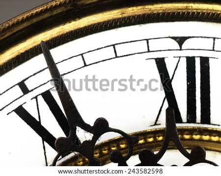 Mechanism of old clock. Clock face and hands showing five minutes to midnight. - stock photo
