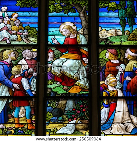 MECHELEN, BELGIUM - JANUARY 31, 2015: Stained Glass window depicting the miracle of Jesus feeding the multitude with loaves of bread and fish in the Cathedral of Saint Rumbold in Mechelen, Belgium. - stock photo