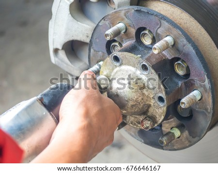 mechenic man fixing a hub cap of losing tire