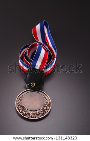 medal with a laurel branch on a striped ribbon