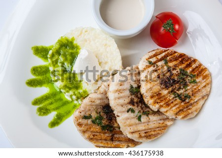 medallions of pork with rice and sauce on plate