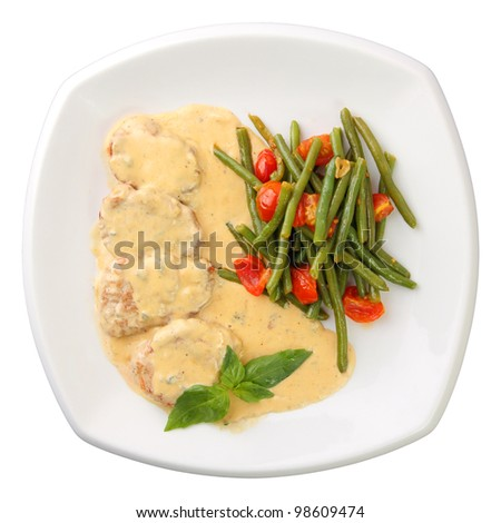 Medallions of veal in a creamy sauce with mushrooms and marinated vegetables on a white background. Top view. - stock photo