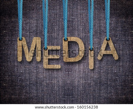 Media Letters hanging strings with blue sackcloth background. - stock photo
