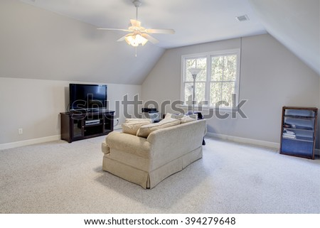 media room in attic of house with windows