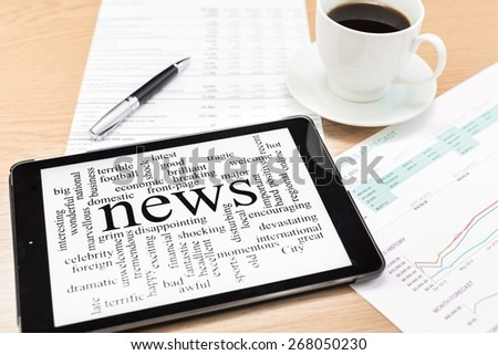Media. Tablet PC shows latest news on screen, which lying on work place. - stock photo