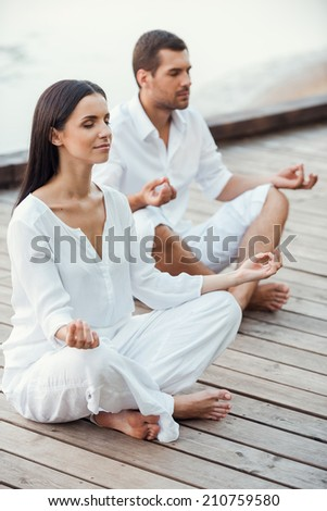Mediating together. Top view of beautiful young couple in white clothing meditating outdoors together and keeping eyes closed - stock photo