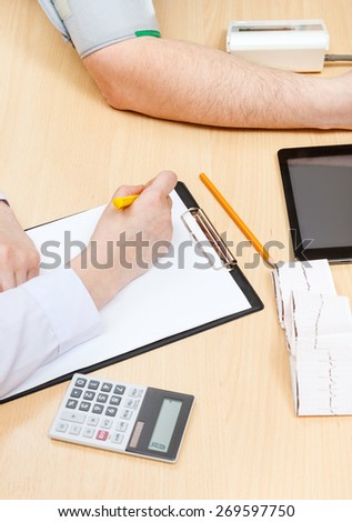 medic makes appointment and measures blood pressure of patient - stock photo