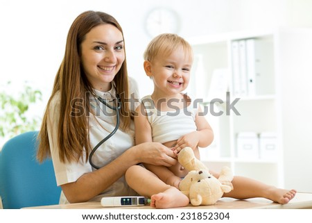 medic pediatrician examining of toddler boy with stethoscope - stock photo