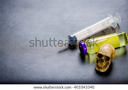 medical ampoules and syringe, skull on black table - stock photo