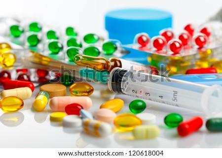 Medical ampoules, syringe and pills isolated on white - stock photo