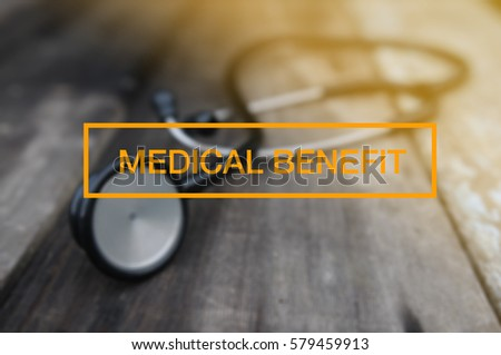 Medical And Health Concept - Stethoscope on vintage wooden table with MEDICAL BENEFIT word. tone image.