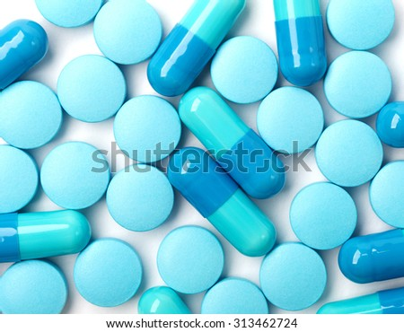 Medical background with blue pills and blue capsules - stock photo