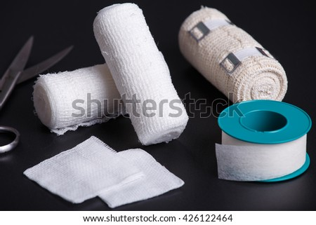 Medical bandages with scissors and sticking plaster - stock photo