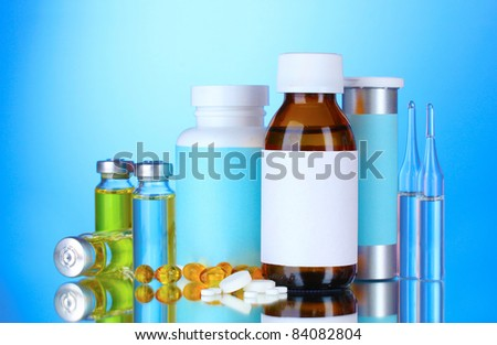 Medical bottles, ampoules and pills on blue background