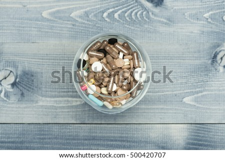 Medical capsules and tablets inside glass on vintage wooden background. Top view