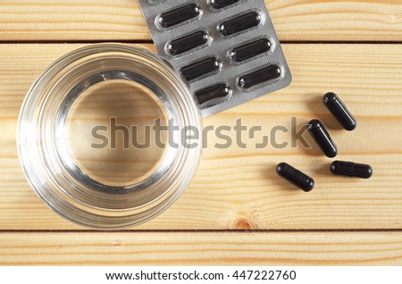 Medical capsules with activated charcoal and glass of water on a wooden background, top view