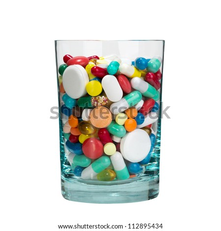 Medical cocktail - glass full of pills. Isolated - stock photo