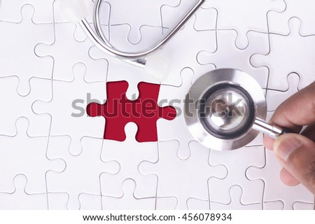 Medical Concept - A doctor holding a Stethoscope on missing puzzle - stock photo
