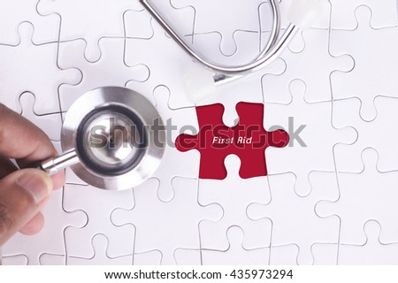 Medical Concept - A doctor holding a Stethoscope on missing puzzle with First Aid WORD - stock photo