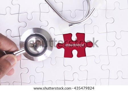 Medical Concept - A doctor holding a Stethoscope on missing puzzle WITH INSURANCE WORD - stock photo