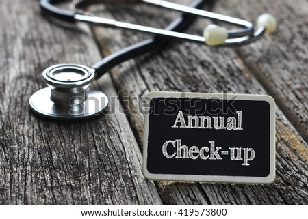 Medical Concept-Annual Check-up word written on blackboard with Stethoscope on wood background - stock photo