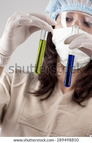 Medical Concept: Female Laboratory Staff Exploring Glass Flask with Color Liquid. Vertical Image Concept - stock photo