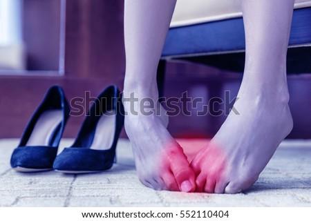 khái niệm y tế.  bánh mì chân.  Vấn đề sức khỏe cơ thể, đôi chân khỏe doanh sưng hoặc mụn nước ở vết thương trên da.  người phụ nữ chân trần đau đớn ở nhà hay văn phòng với đôi giày cao gót cao trong nền