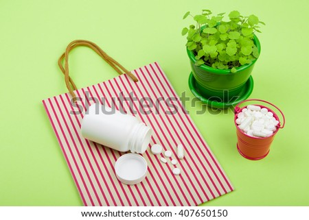 Medical concept - many different pills in a pink bucket, striped shopping bag and container of pills on green background - stock photo